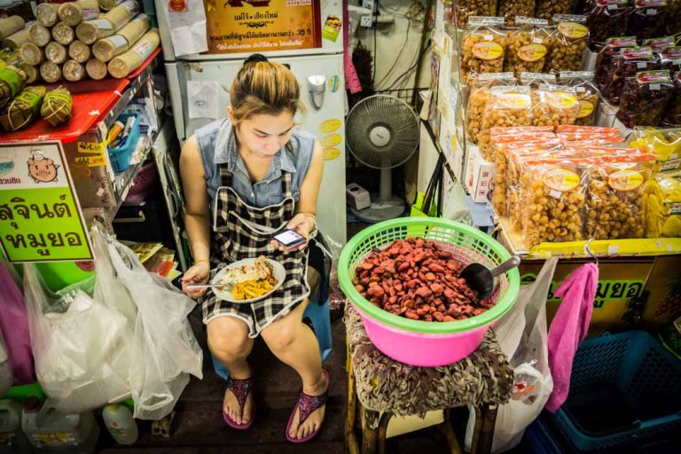 A girl reading her mobile while eating in a food stall in Worarot Market. Chiang Mai, Thailand.