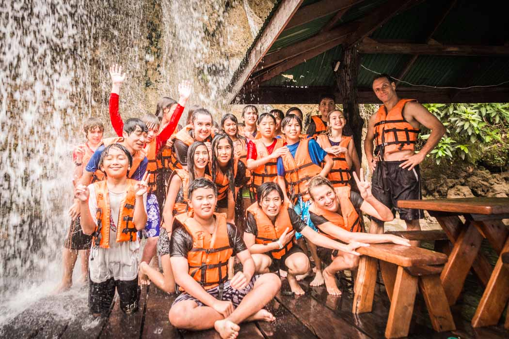 The students and the tutors under a waterfall in Say Yok National Park.
