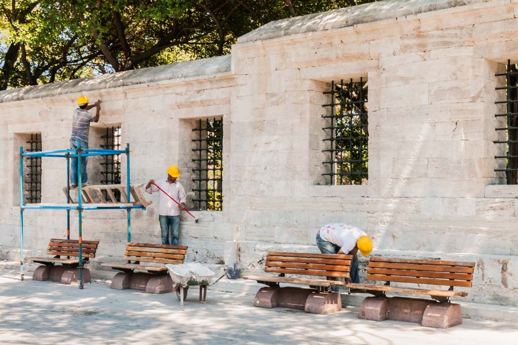 Three men restoring a wall in Istanbul, Turkey.
