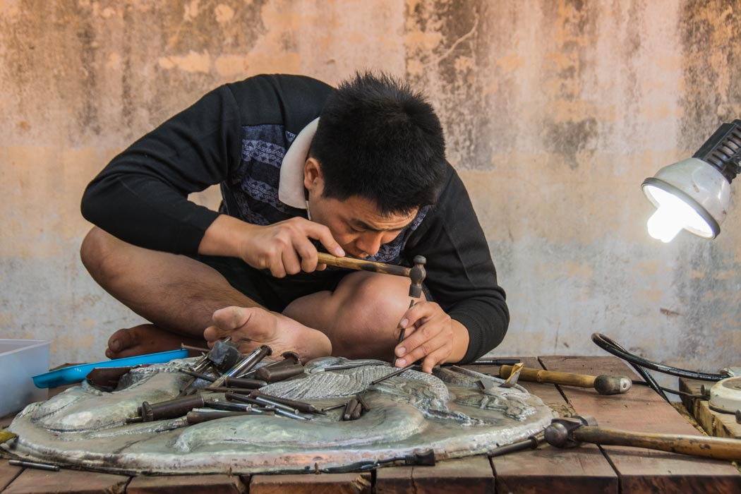 Silver craftsman at work on a new tableau, in Chiang Mai, Thailand.