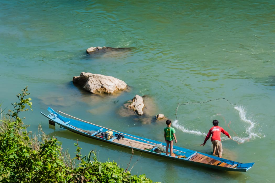 A fisherman throwing his net in the Nam Khan river in Luang Prabang, Laos.