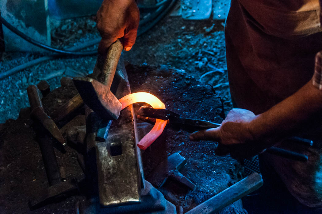 A blacksmith working on a horseshoe in Chirpar, Romania.